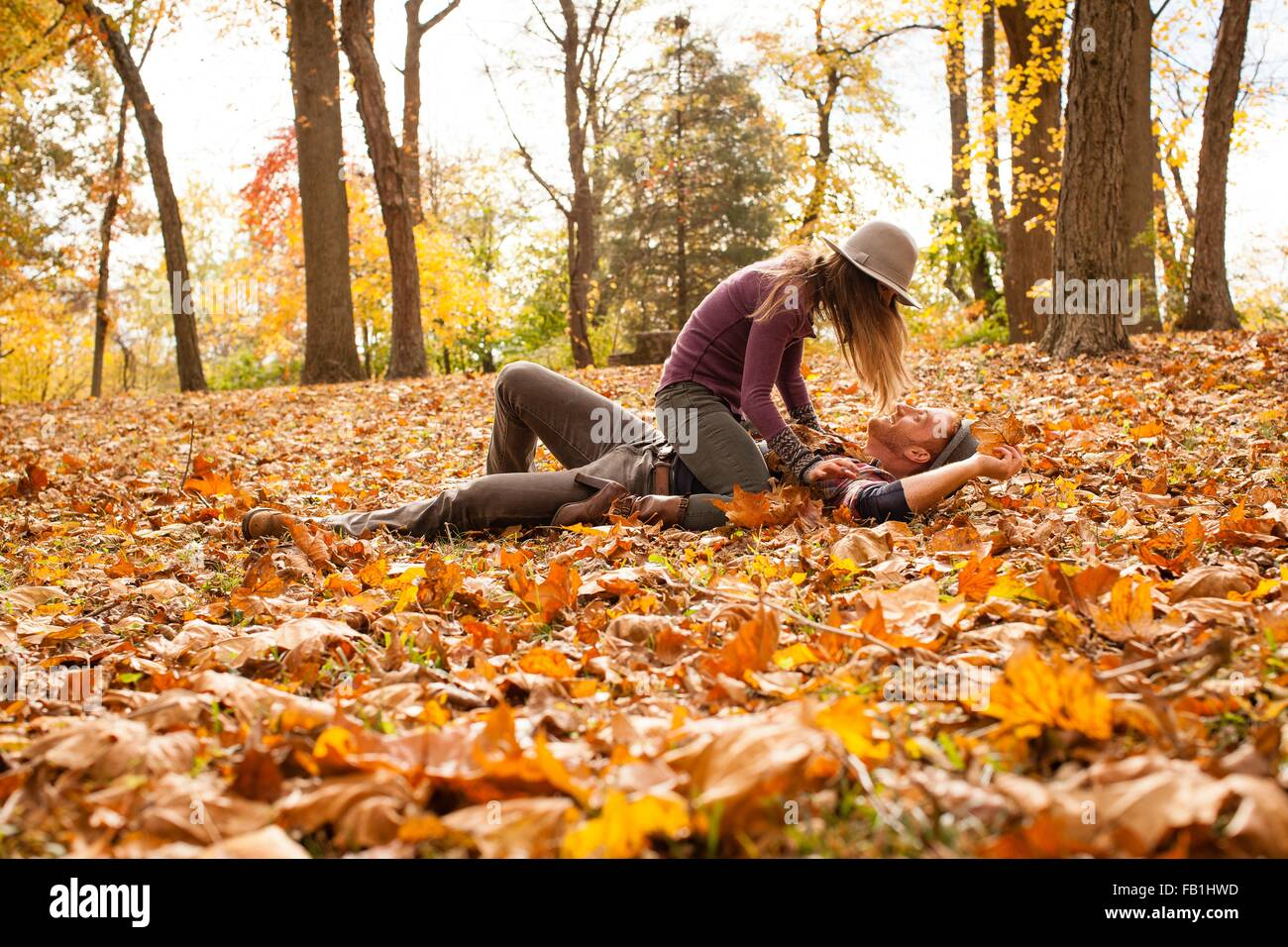 Young couple play fighting on autumn forest floor - Stock Image