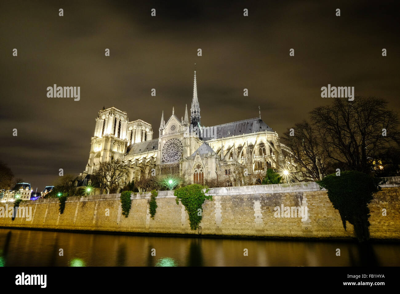 A beautiful night scene of Cathedral Notre Dame along the Seine in Paris France. - Stock Image