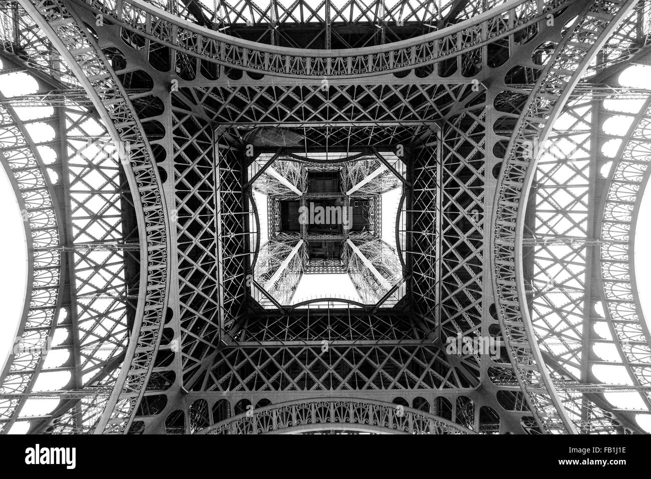 A photograph from below the bottom of the Eiffel tower in Paris France.  Black and White. - Stock Image