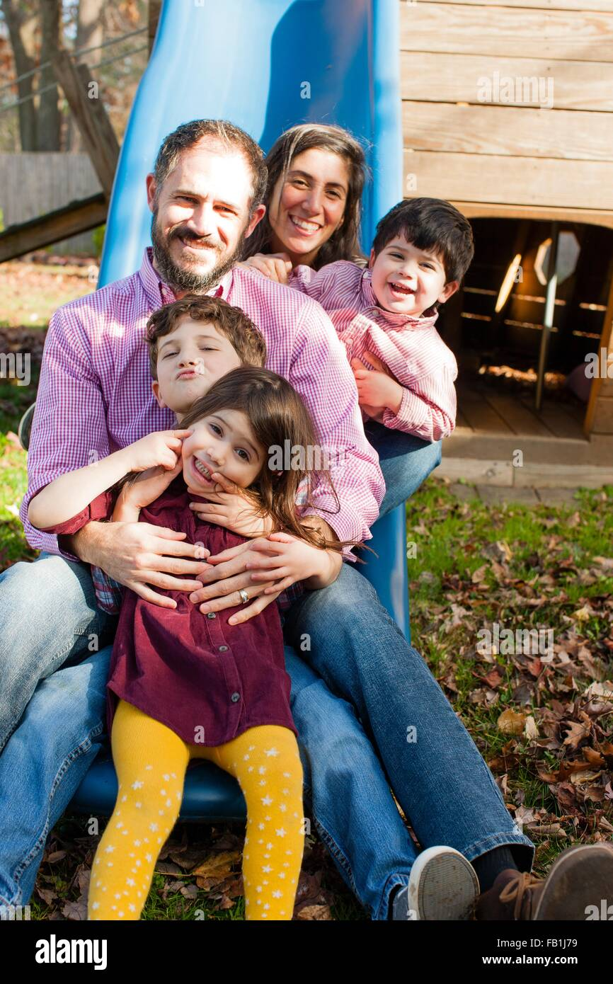 Family in a row between each others legs on playground slide, looking at camera smiling Stock Photo