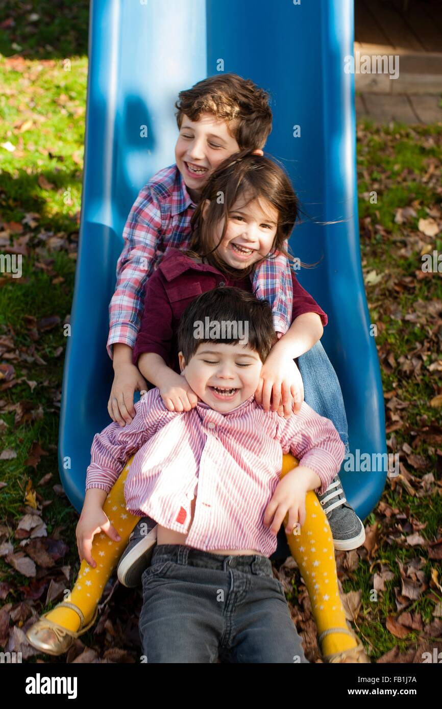 Siblings in a row between each others legs on playground slide smiling - Stock Image