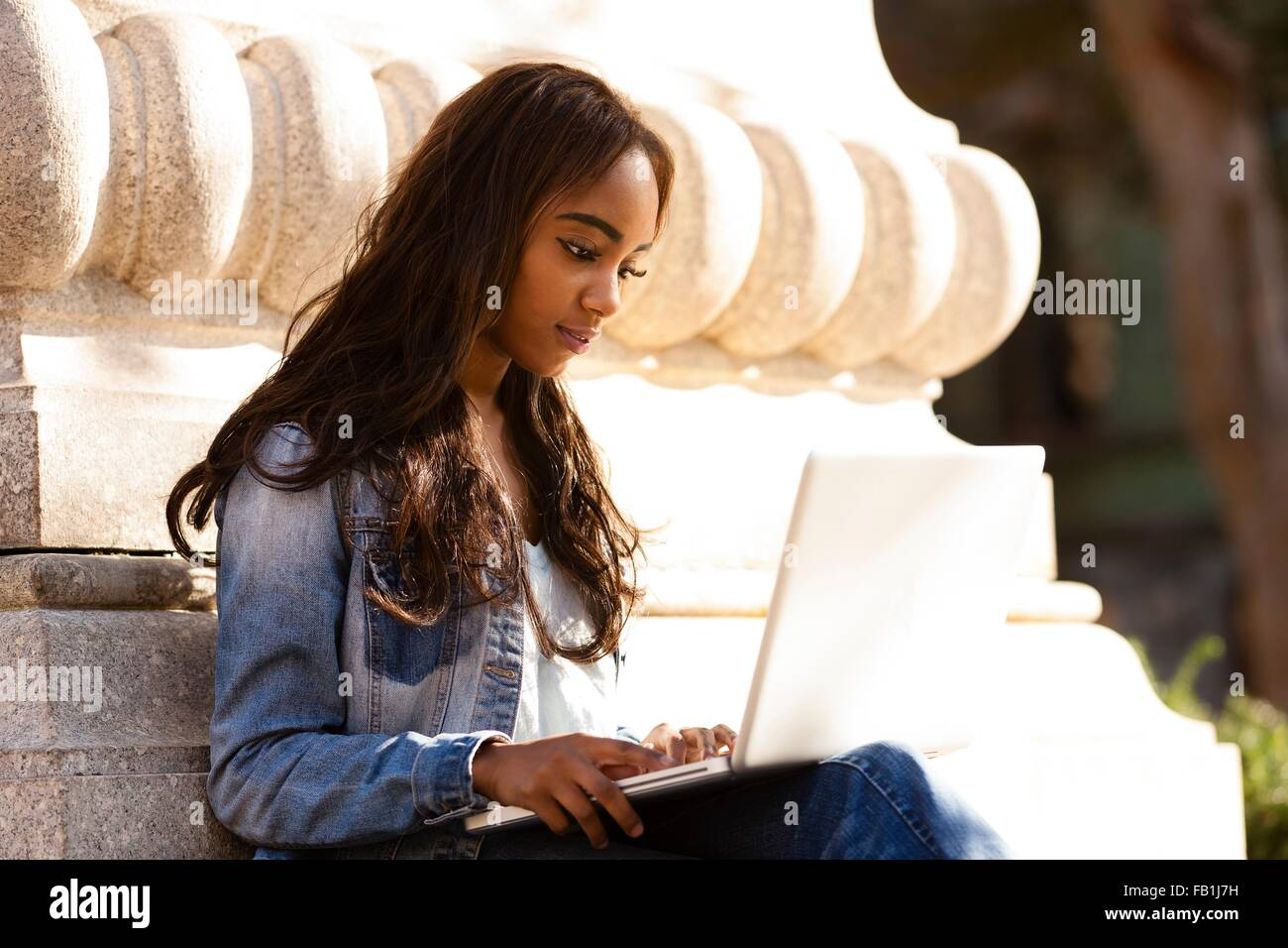 Young woman sitting leaning against stone carving looking down using laptop computer - Stock Image