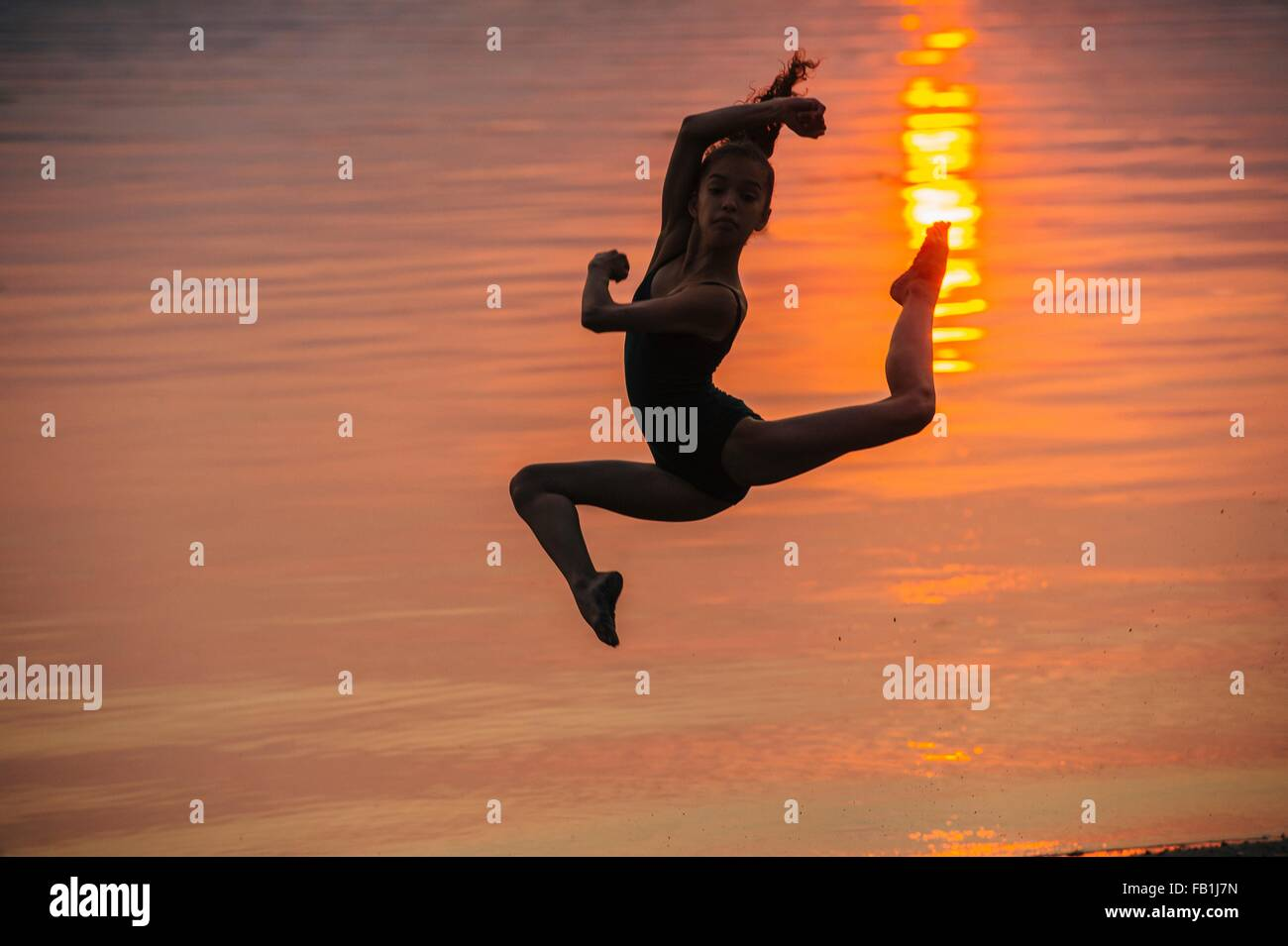 Side view of girl in silhouette by ocean at sunset leaping in mid air, legs apart looking at camera Stock Photo