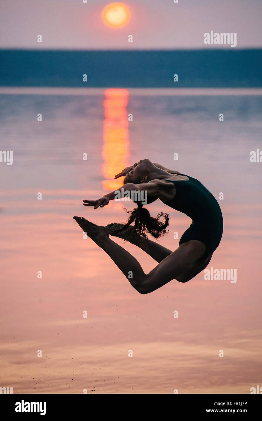 Side view of girl by ocean at sunset, leaping in mid air bending backwards - Stock Image