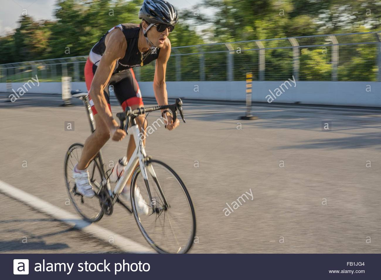Mid adult man cycling on mountain bike on race track, burred motion, Montreal, Quebec, Canada - Stock Image