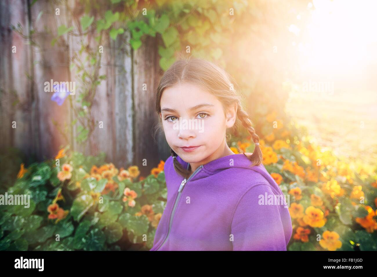 Portrait of girl with plaits in front of orange flowers looking at camera - Stock Image