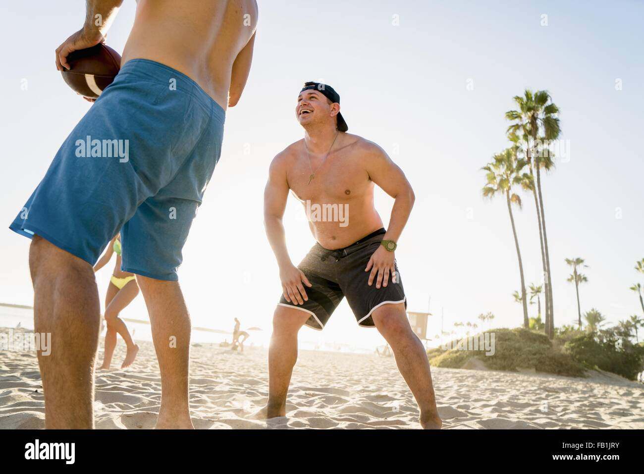 Male and female friends playing American football on Newport Beach, California, USA - Stock Image