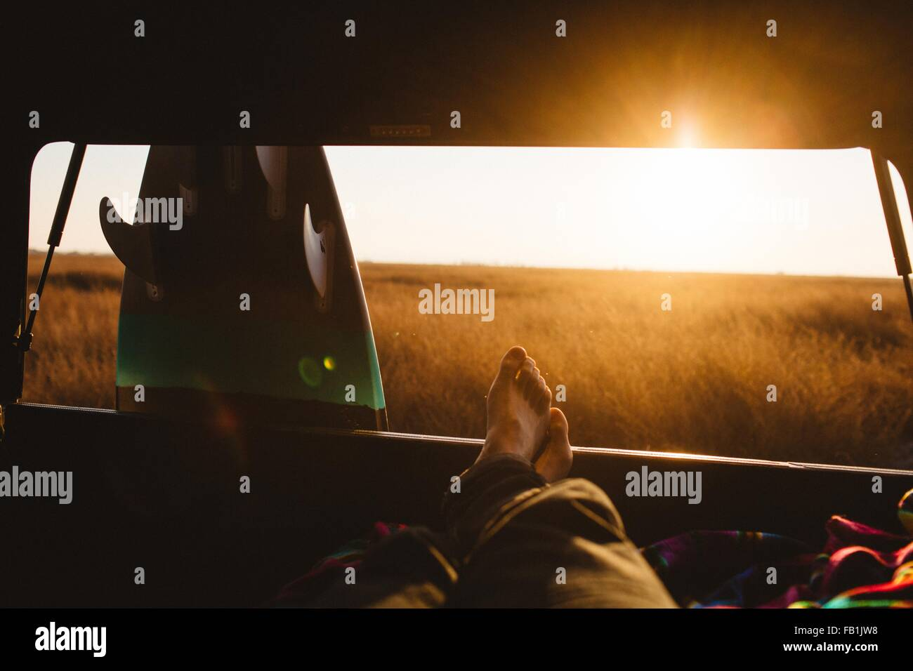 Male surfer with bare feet up in back of jeep at sunset, San Luis Obispo, California, USA - Stock Image