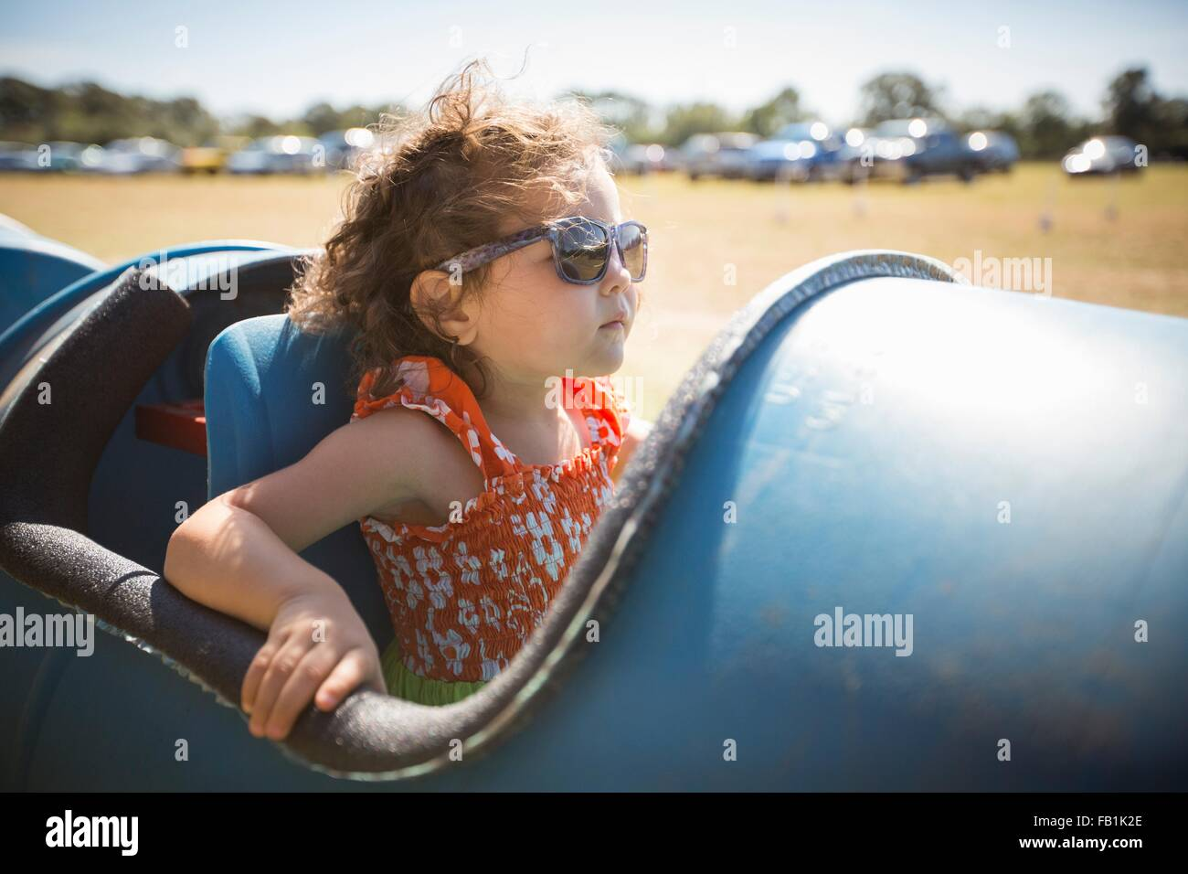 Girl sitting in barrel cart, wearing sunglasses looking away - Stock Image