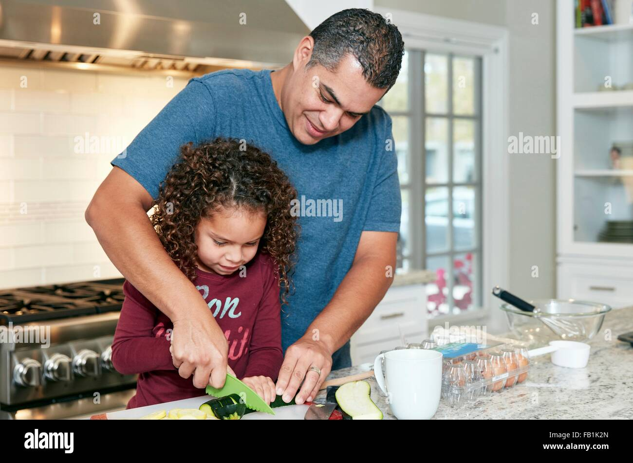 Father helping daughter chop vegetables in kitchen - Stock Image