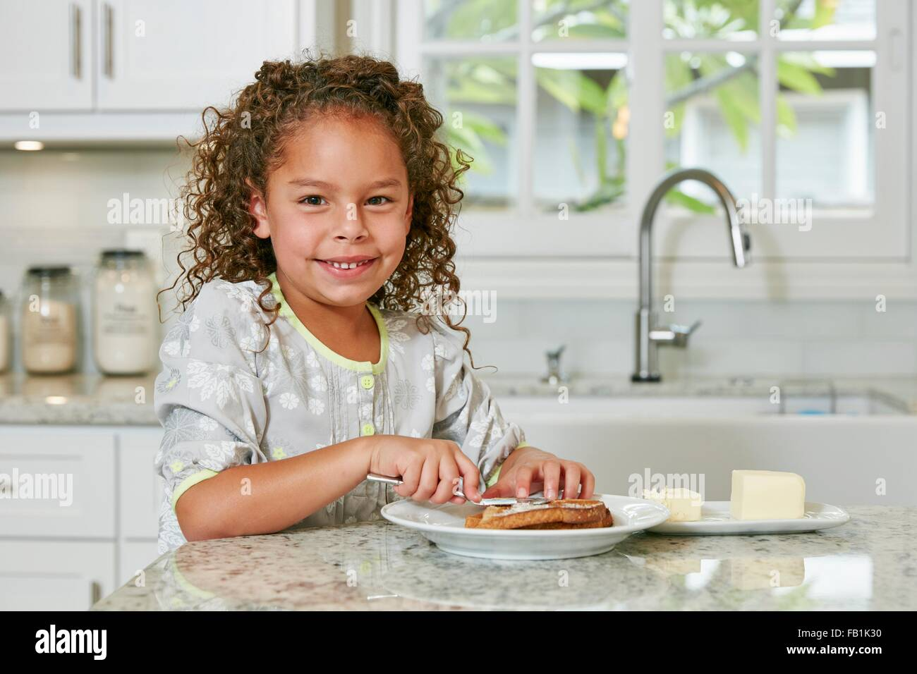 Girl at kitchen counter spreading butter on toast looking at camera smiling - Stock Image
