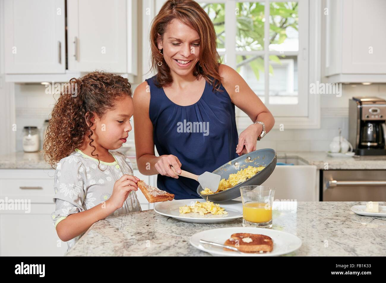 Mother at kitchen counter serving daughter scrambled eggs from frying pan - Stock Image