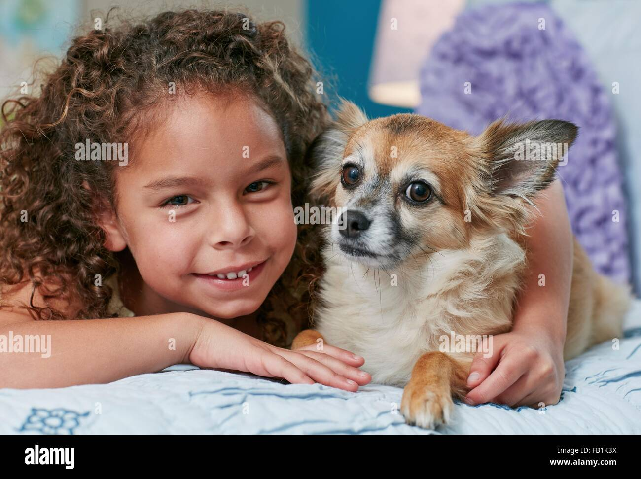 Girl lying on bed arm around dog, looking at camera smiling Stock Photo