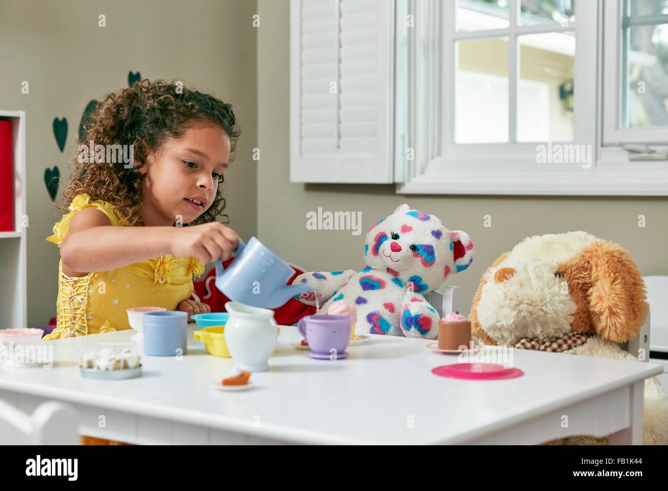 Girl in playroom sitting at table serving tea from toy tea set to ...