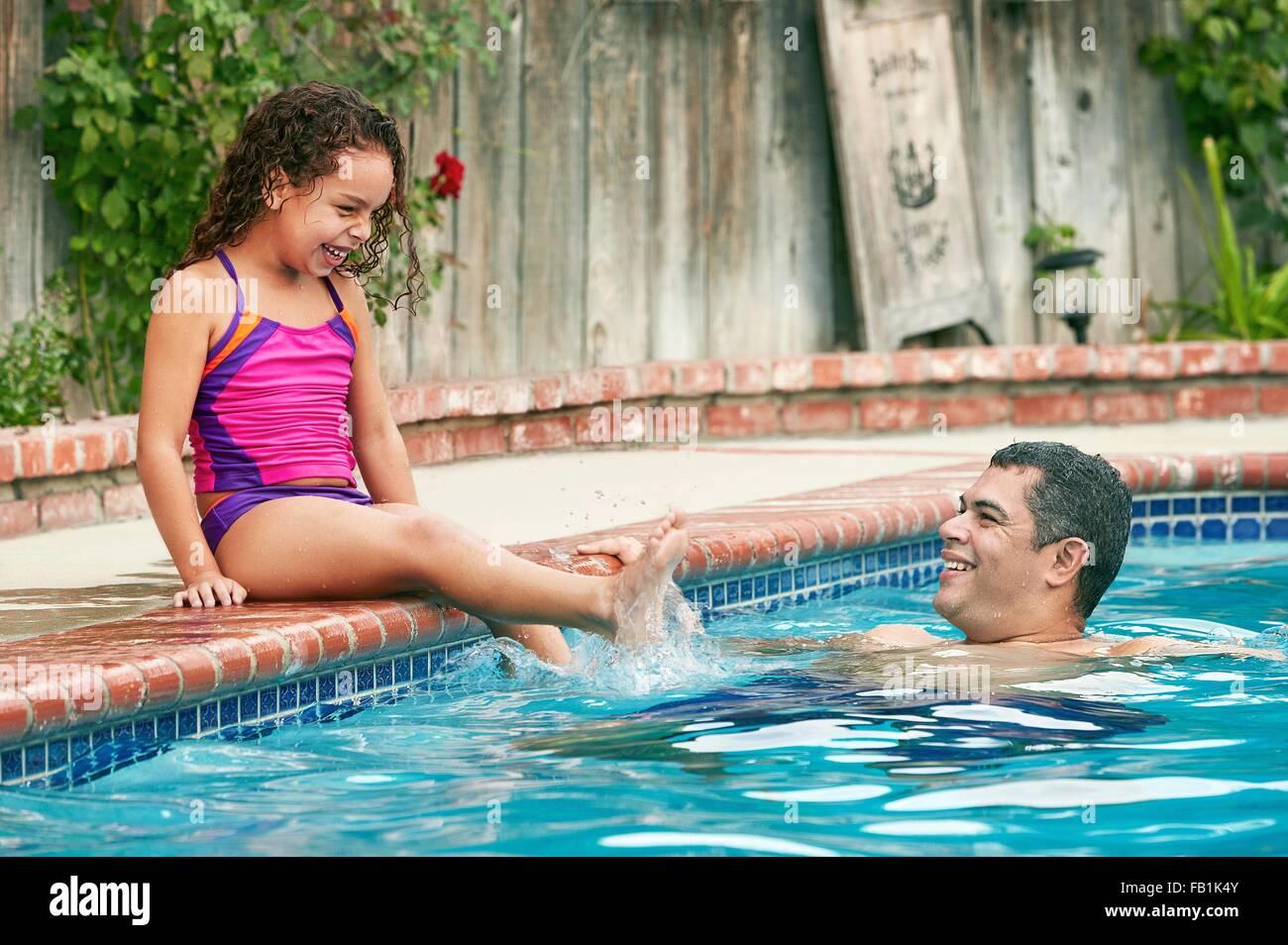 Girl wearing swimwear sitting poolside splashing father smiling - Stock Image