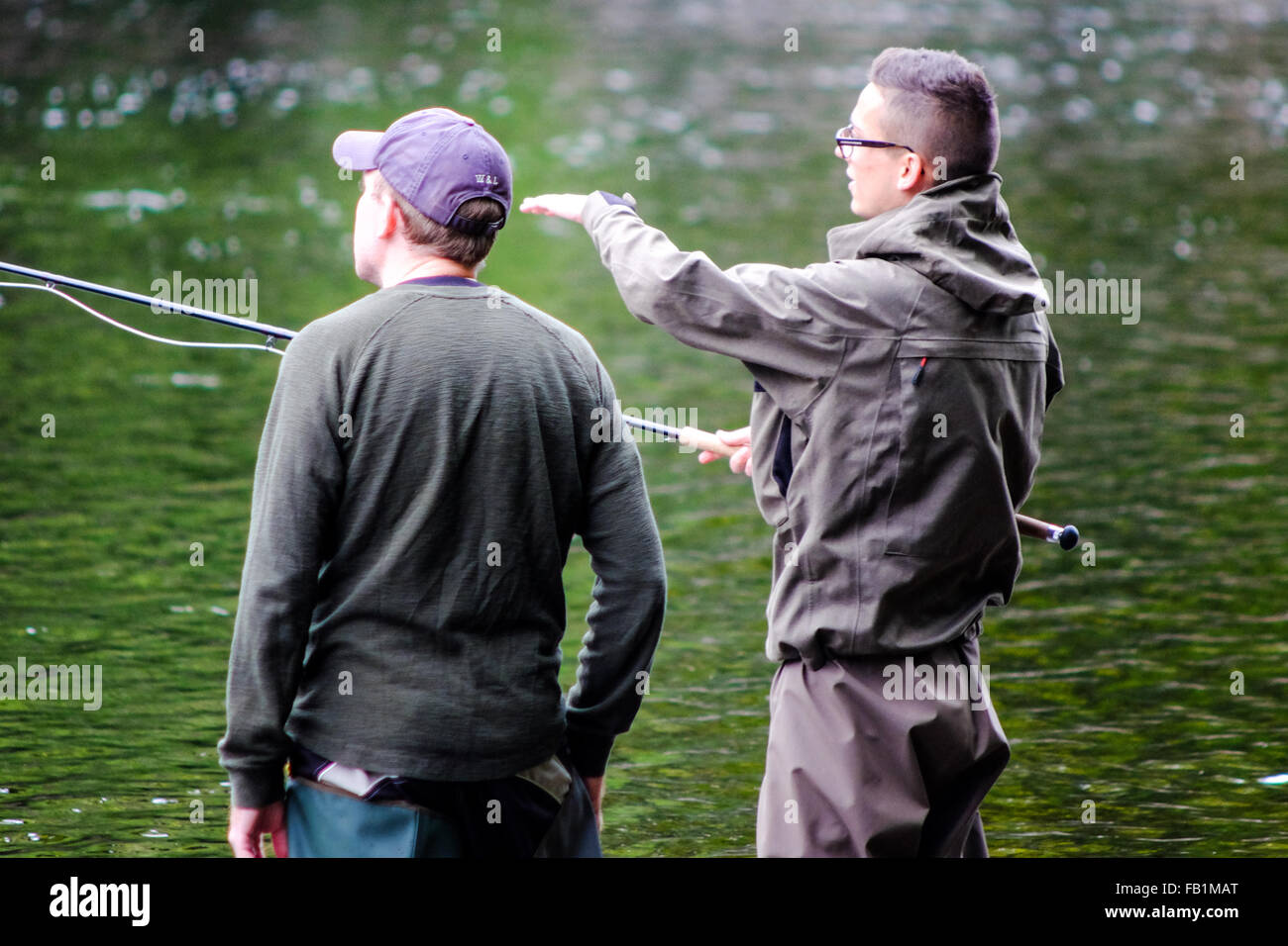 Fly fishing young men learn to fish on the Ness River in Inverness Scotland. - Stock Image