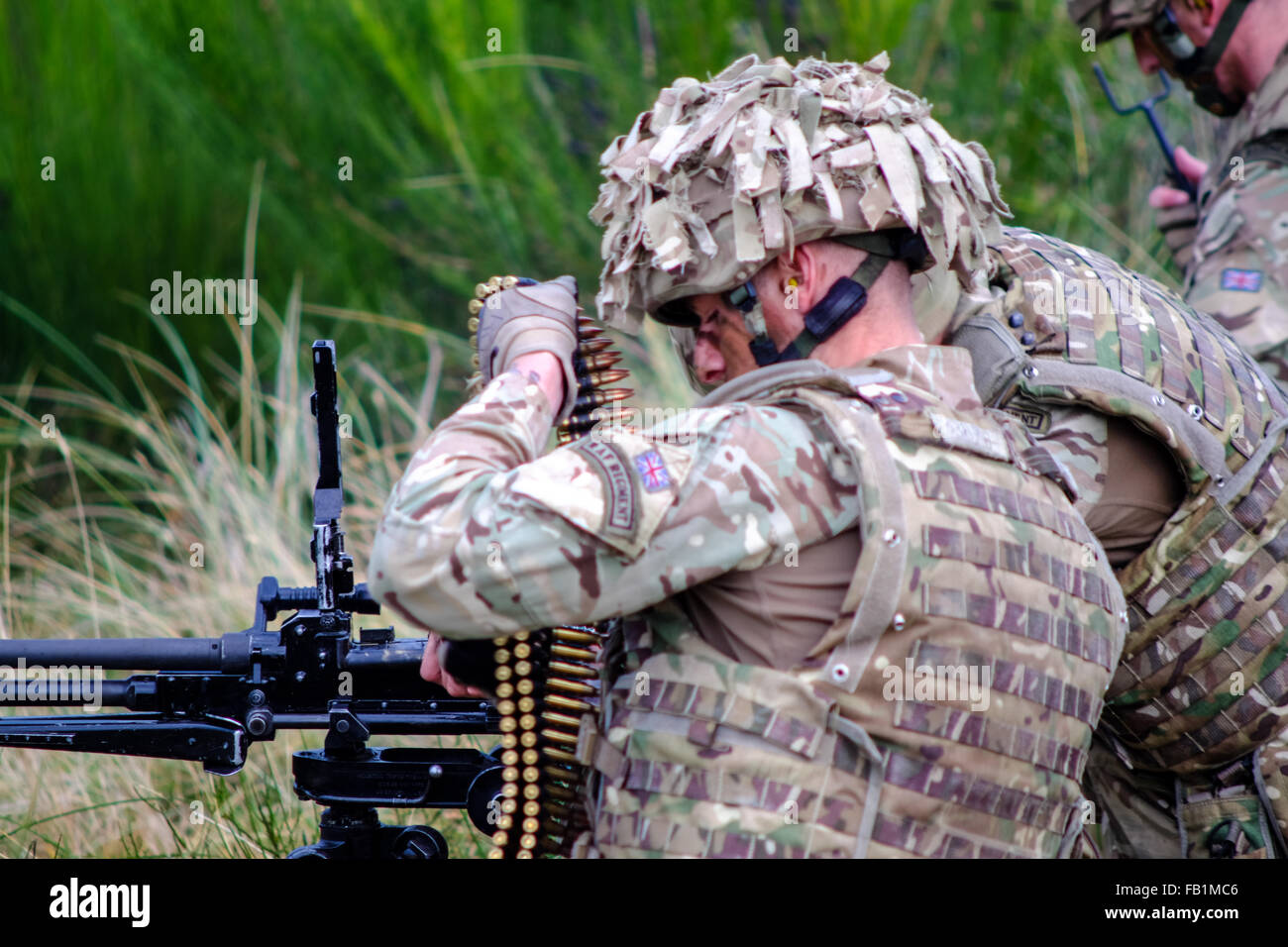 A Royal Air Force RAF regiment soldier loads a machine gun during a drill at Fort George, Scotland. - Stock Image
