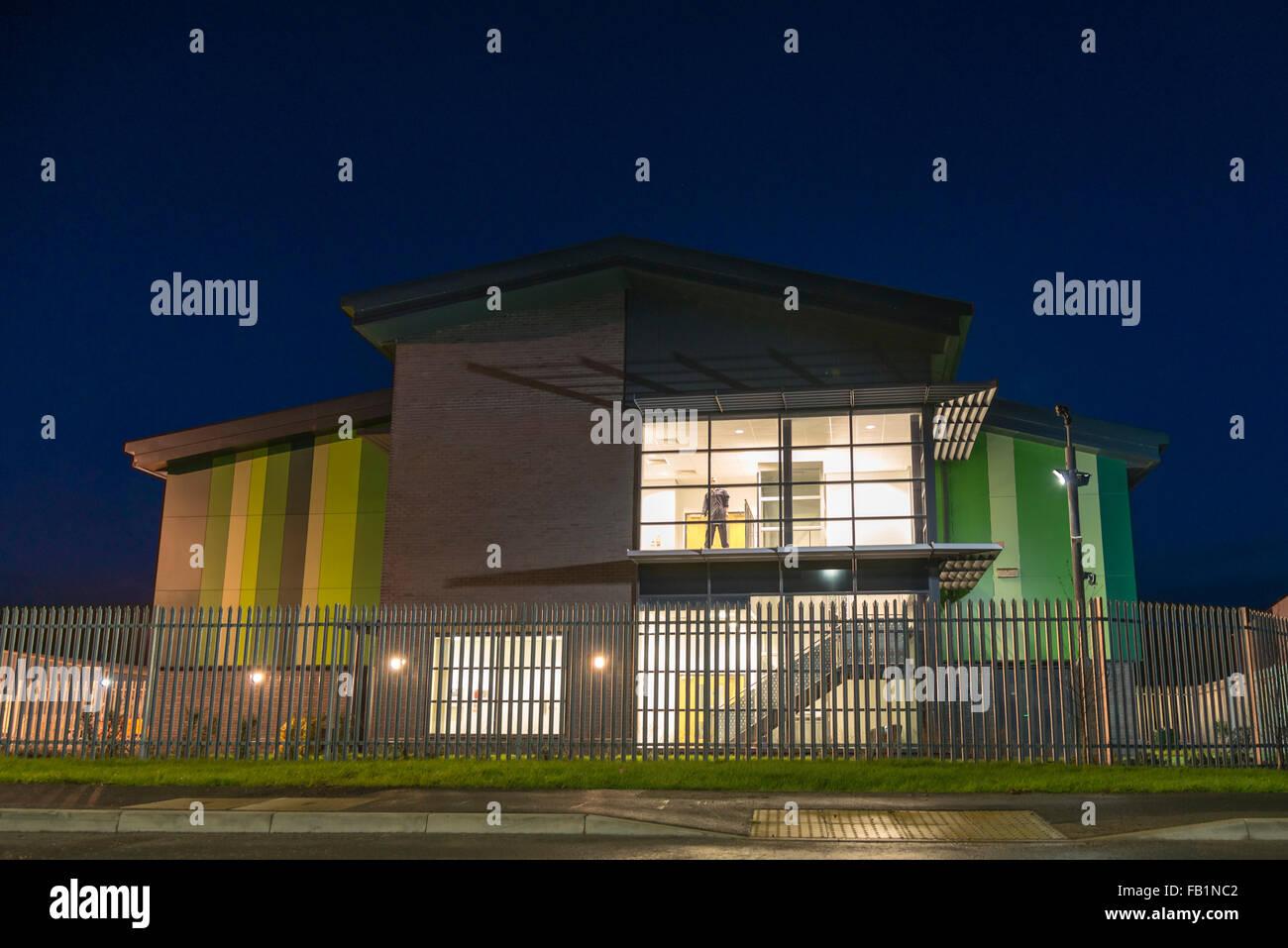 Commercial real estate industrial unit exterior taken at dusk, UK. Mannequin at window. - Stock Image