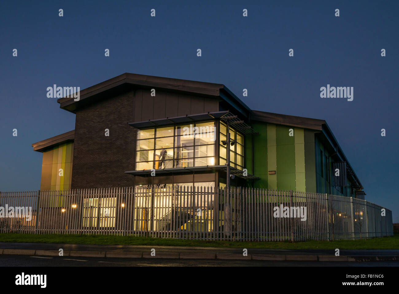 Commercial real estate industrial unit exterior taken at dusk, UK. Mannequin in window. - Stock Image