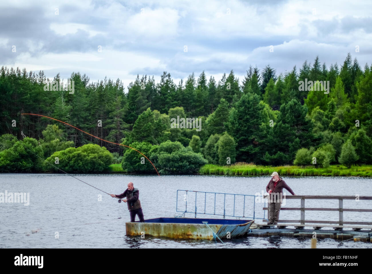 Scottish men fly fishing on a pier in Moy, in the highlands of Scotland. - Stock Image
