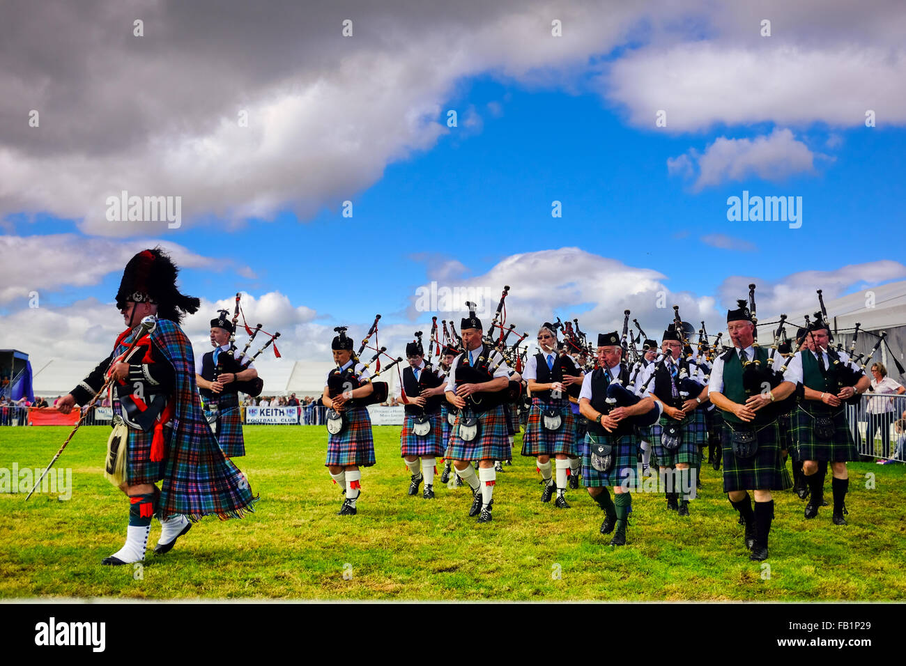 Scottish Bagpiper band marching during summer Scottish Games in Keith, Scotland, United Kingdom wearing tartan kilts. - Stock Image