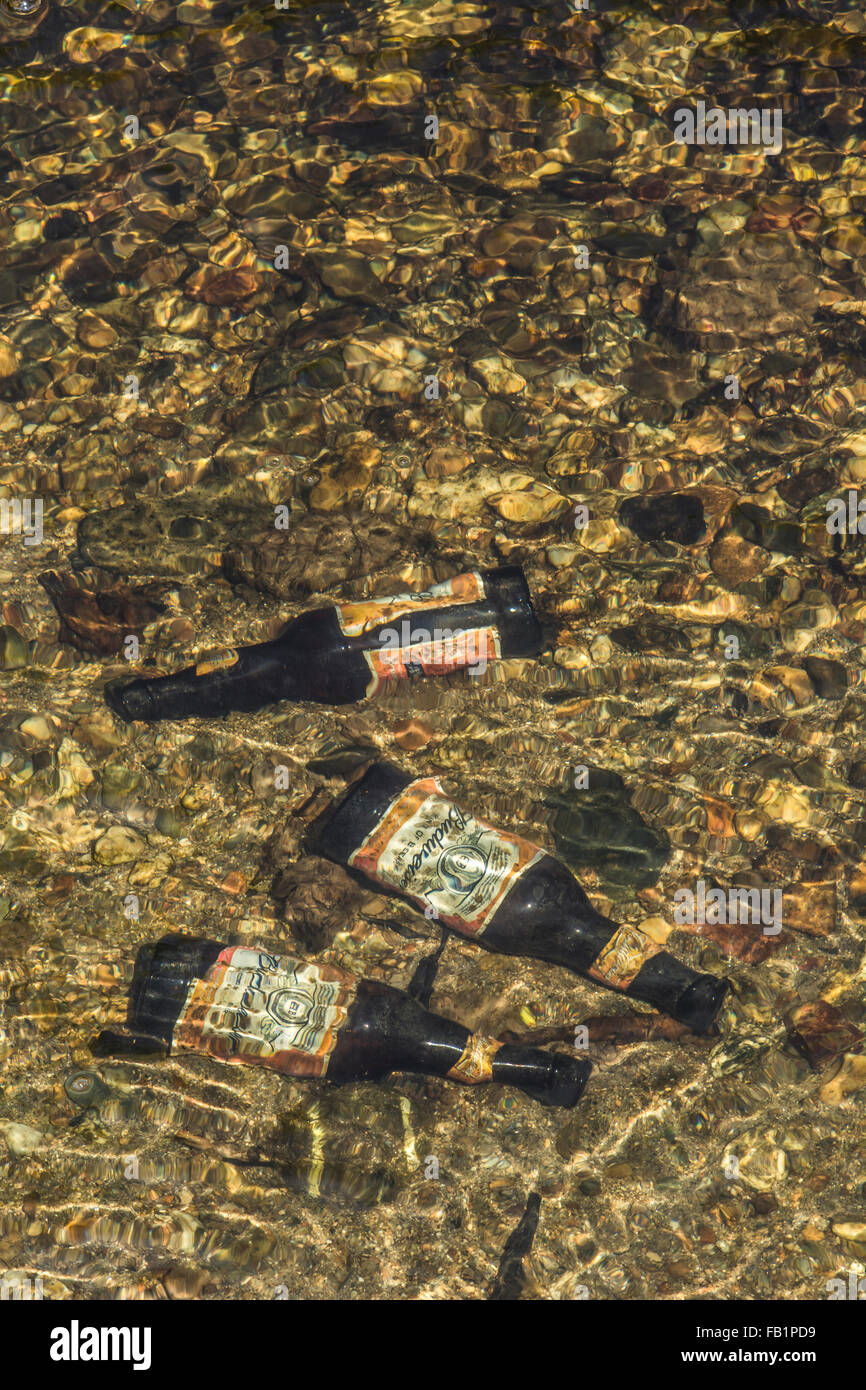 Three empty beer bottles discarded on the bed of a freshwater river. Metaphor environmental pollution. - Stock Image