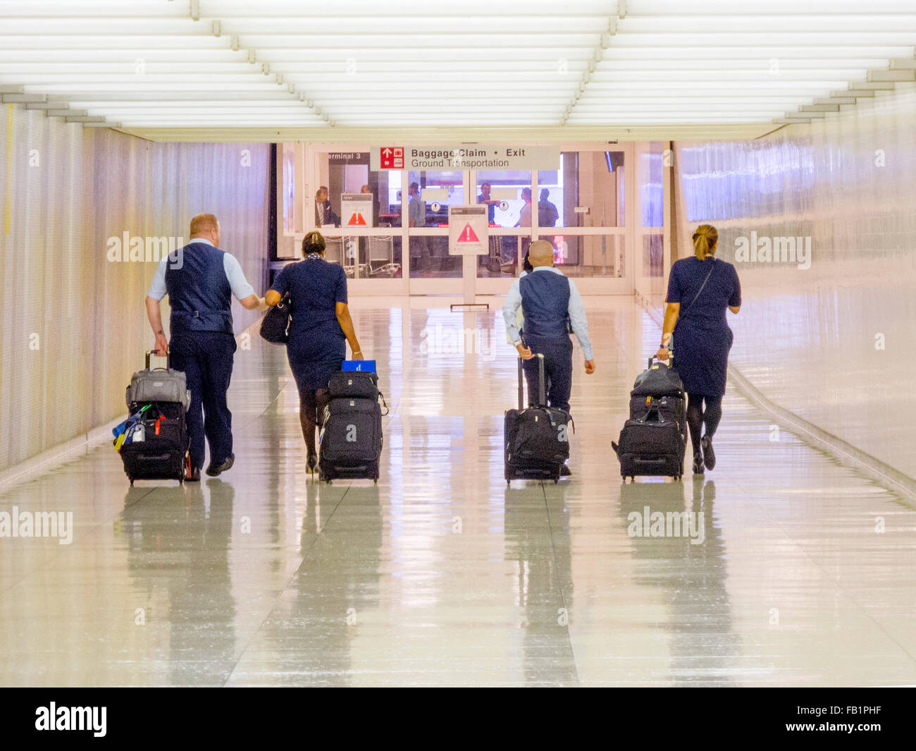 Carrying their luggage on rolling carts, a uniformed aircrew heads for the arrival gate at Los Angeles International - Stock Image