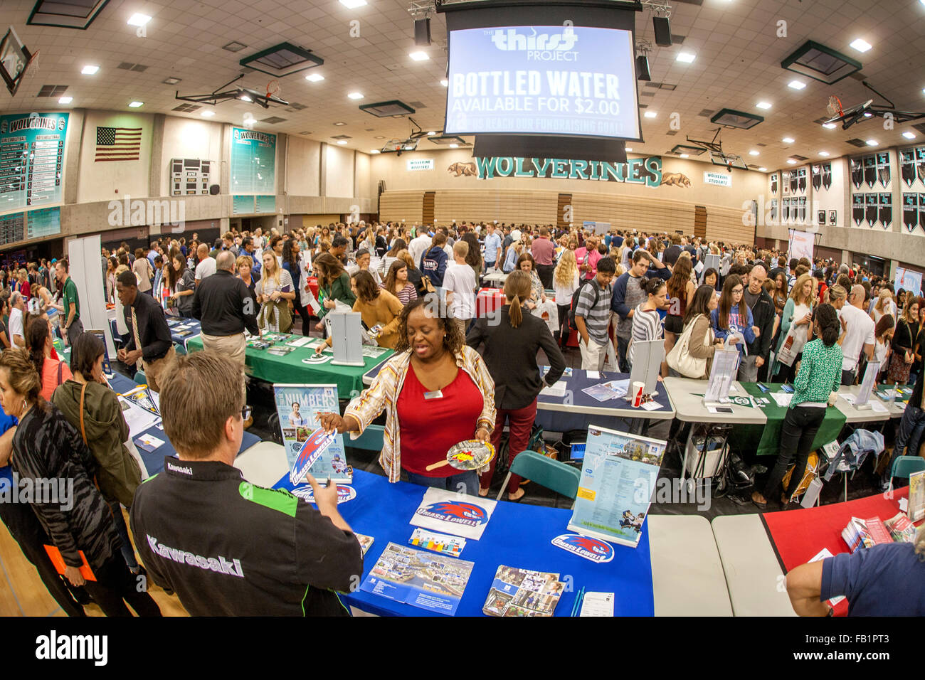 Multiracial high school students attend a college fair in an Aliso Viejo, CA, school gymnasium. Note college recruiters, - Stock Image