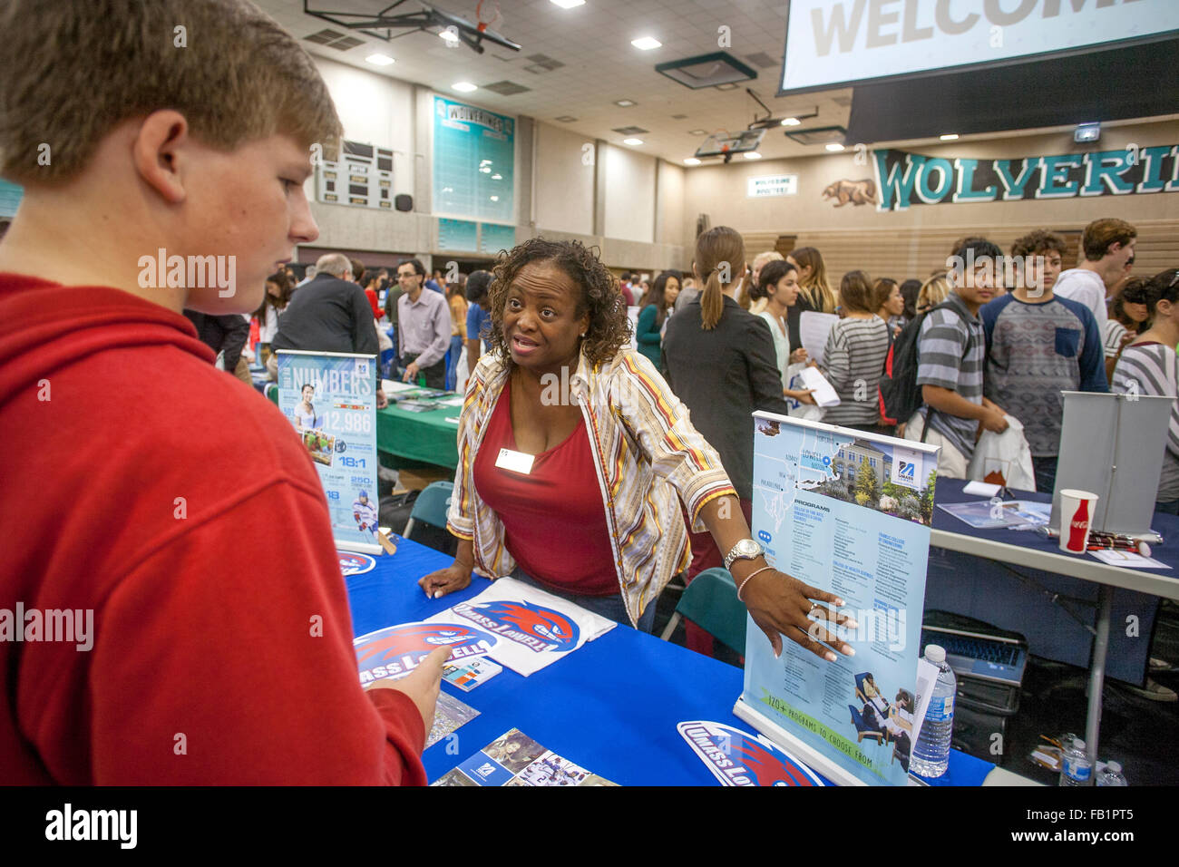Multiracial high school students attend a college fair in an Aliso Viejo, CA, school gymnasium. Note college recruiter - Stock Image