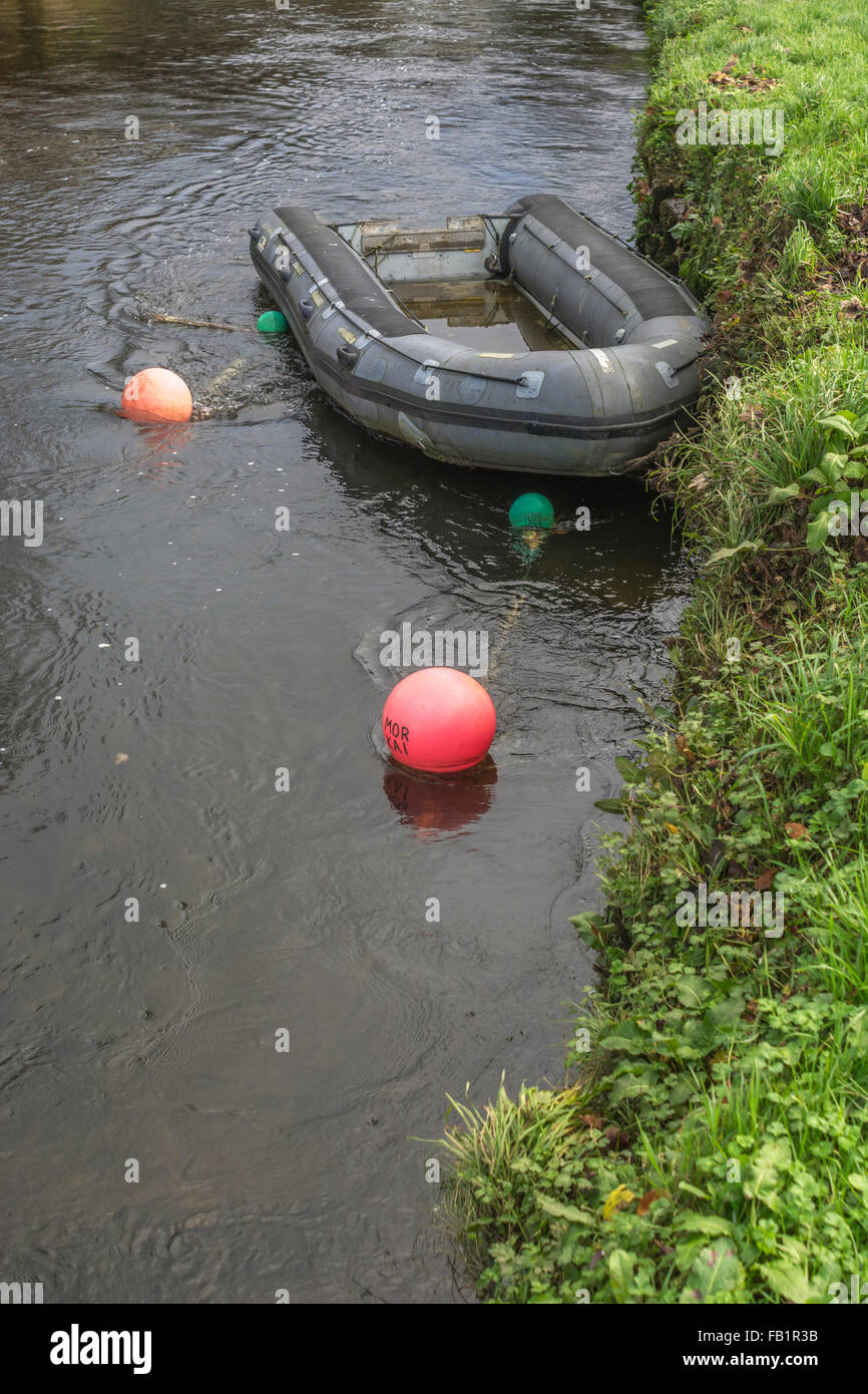Inflatable dinghy moored at river's edge (River Fowey, Lostwithiel). Visual metaphor for recreation time, leisure - Stock Image