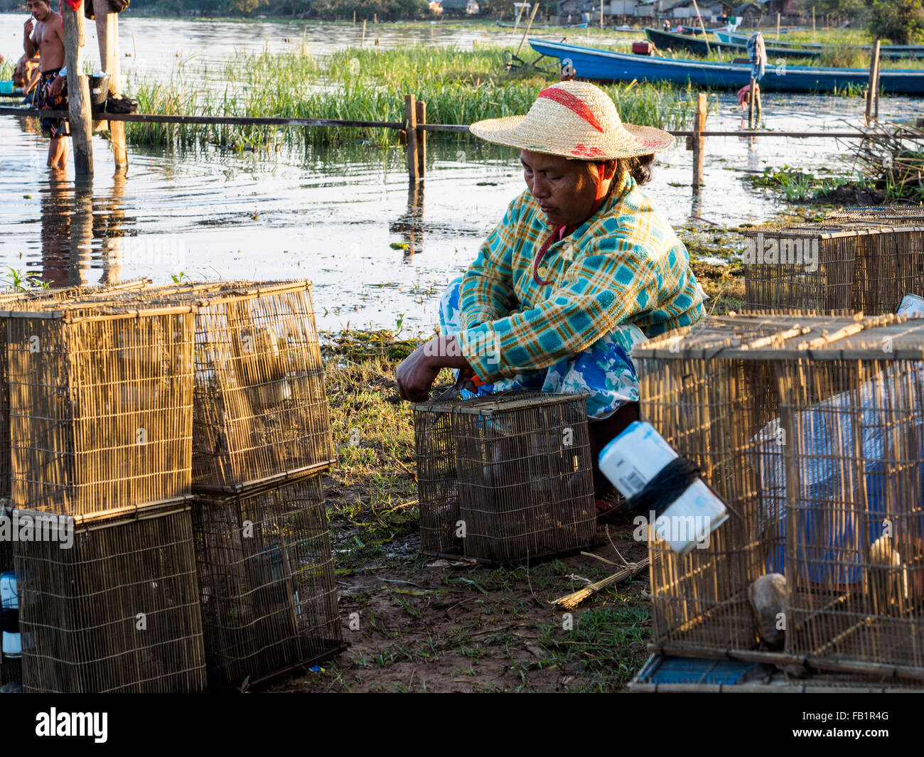 A local woman preparing fishing tool on the lake side. Stock Photo