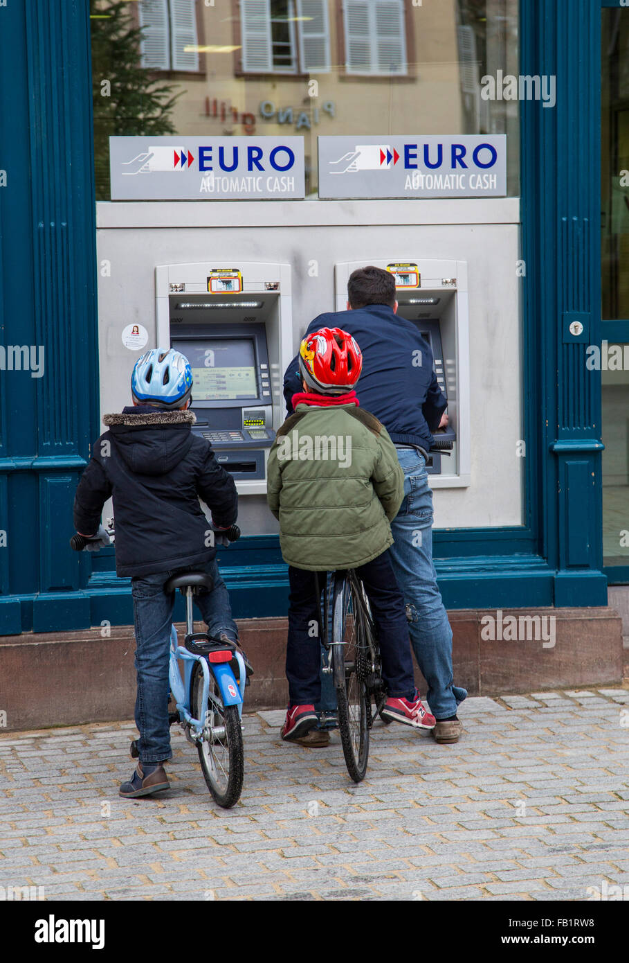 Person with 2 kids at a banking machine, getting cash - Stock Image