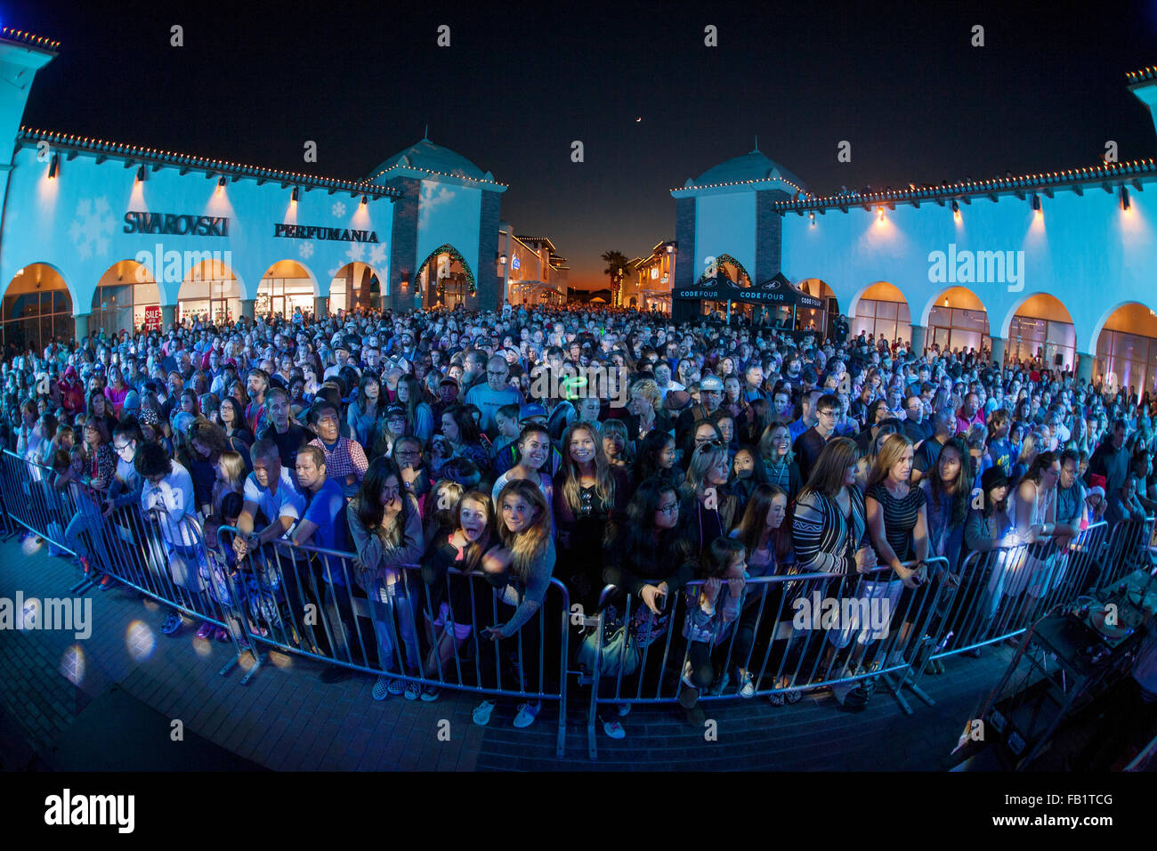 A large audience attends a night time Christmas rock 'n' roll concert at a San Clemente, CA, shopping mall. - Stock Image