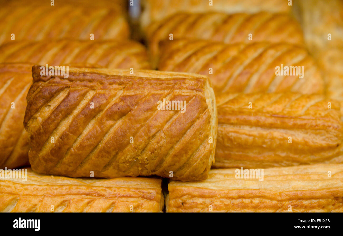 Cooked fresh sausage rolls on display in a butchers shop - Stock Image
