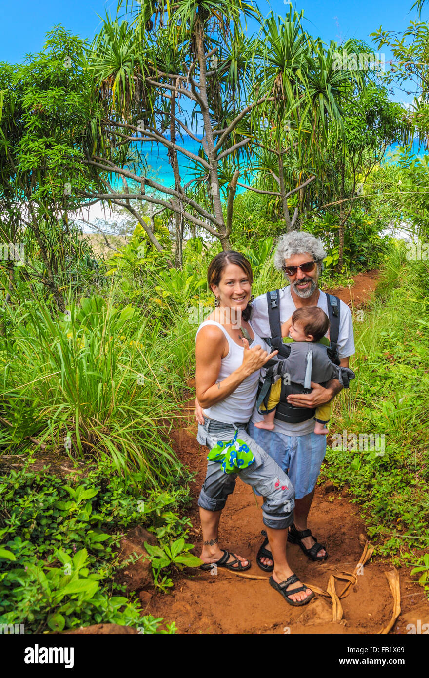 Couple with baby on the Kalalau Trail, with Hanakapiai Beach in background Stock Photo