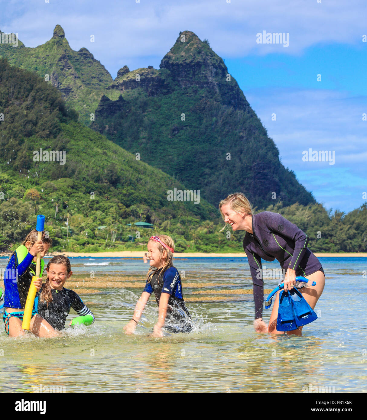 Family having fun splashing at Tunnels Beach on Kauai, with Mt. Makana, called Bali Hai, in distance - Stock Image