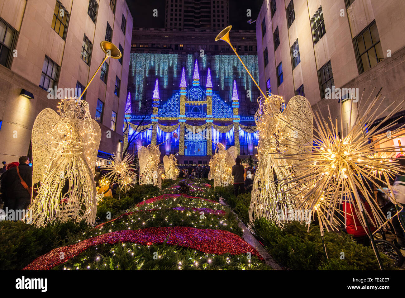 Christmas Angels at Rockefeller Center Channel Gardens with Saks department store's Christmas light show behind, - Stock Image