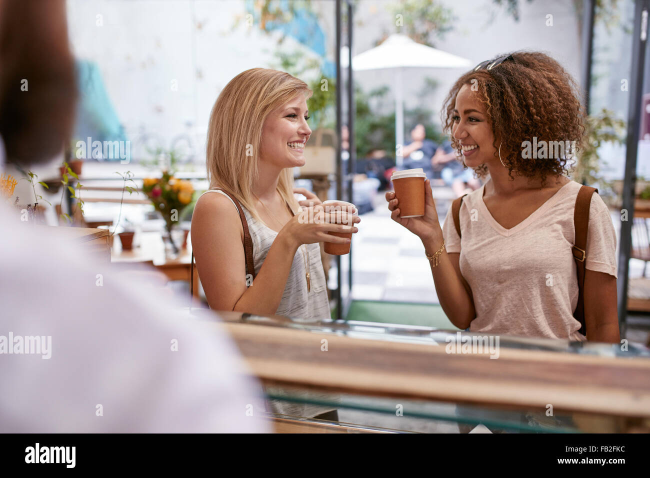 Indoor shot of two young female friends having a cup of coffee at cafe. Women at restaurant drinking hot coffee - Stock Image