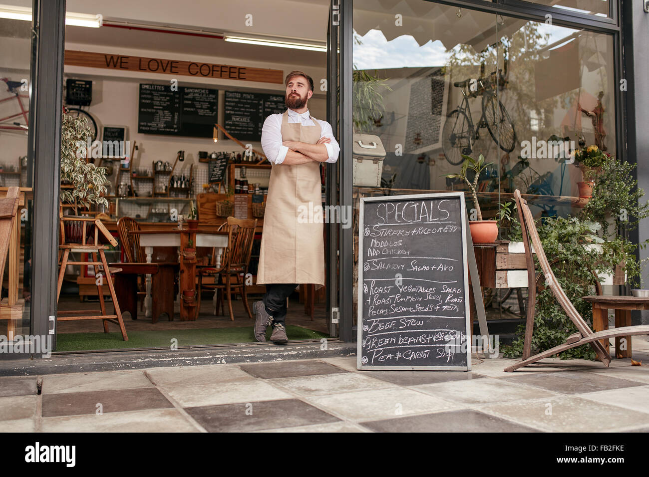 Full length shoot of a young barista standing in door of a coffee shop. Young man with beard wearing an apron standing - Stock Image