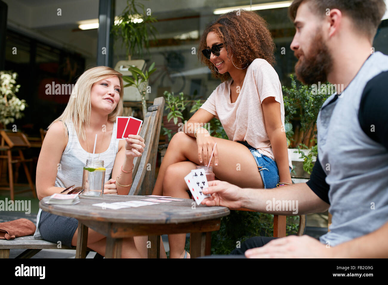 Young people playing cards at sidewalk cafe. Three friends playing poker at outdoor coffee shop. - Stock Image