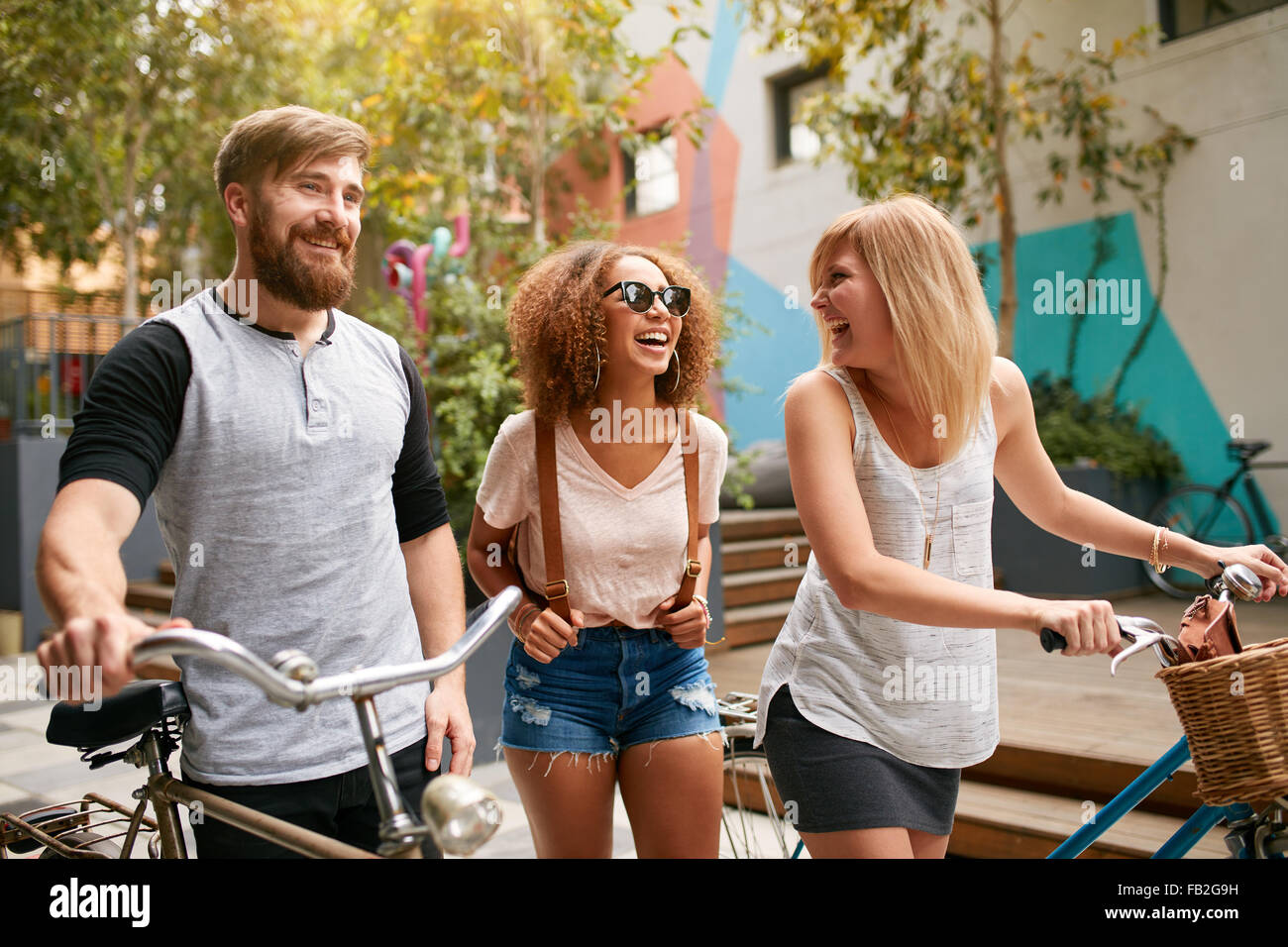 Mixed raced group of friends commuting in city. Three young people walking with their bicycles and having fun. - Stock Image