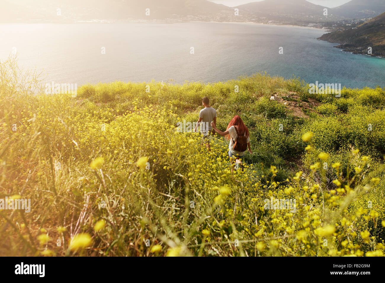 Couple hiking towards the coastline, walking on pathway through grassland, on a summer day. - Stock Image