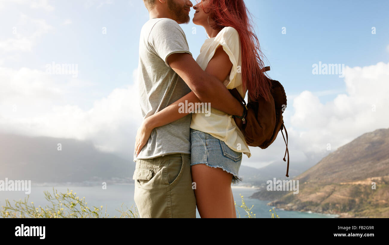 Cropped shot of young man and woman standing close to each other face to face. Romantic couple embracing outdoors. - Stock Image