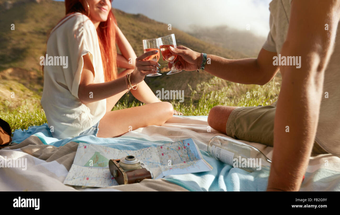 Cropped shot of a man and woman toasting wine while on a picnic. Young couple enjoying a picnic outdoors with wine - Stock Image