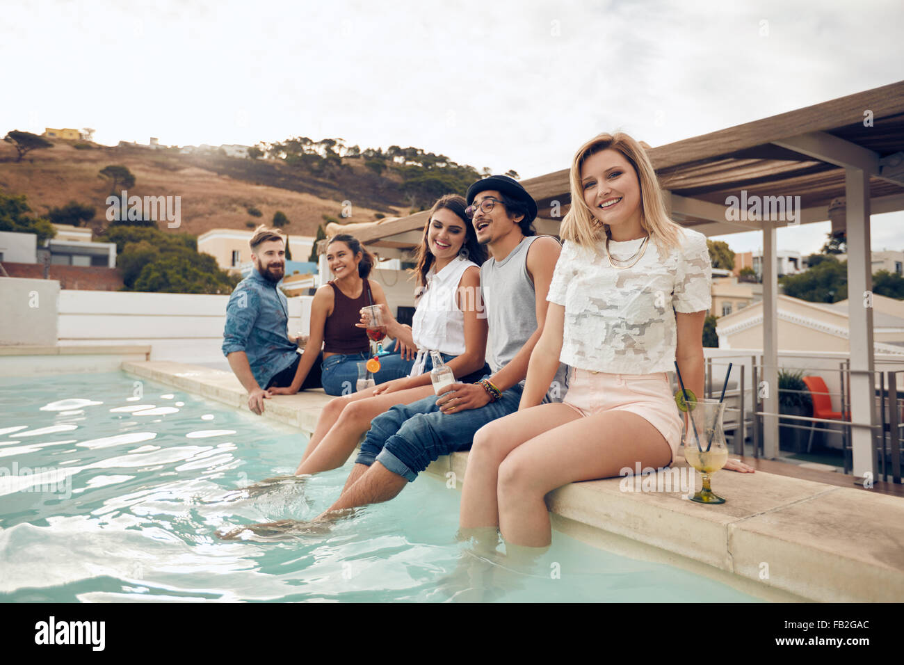 Smiling young woman looking at camera with her friends sitting on the edge of swimming pool. Young people enjoying Stock Photo