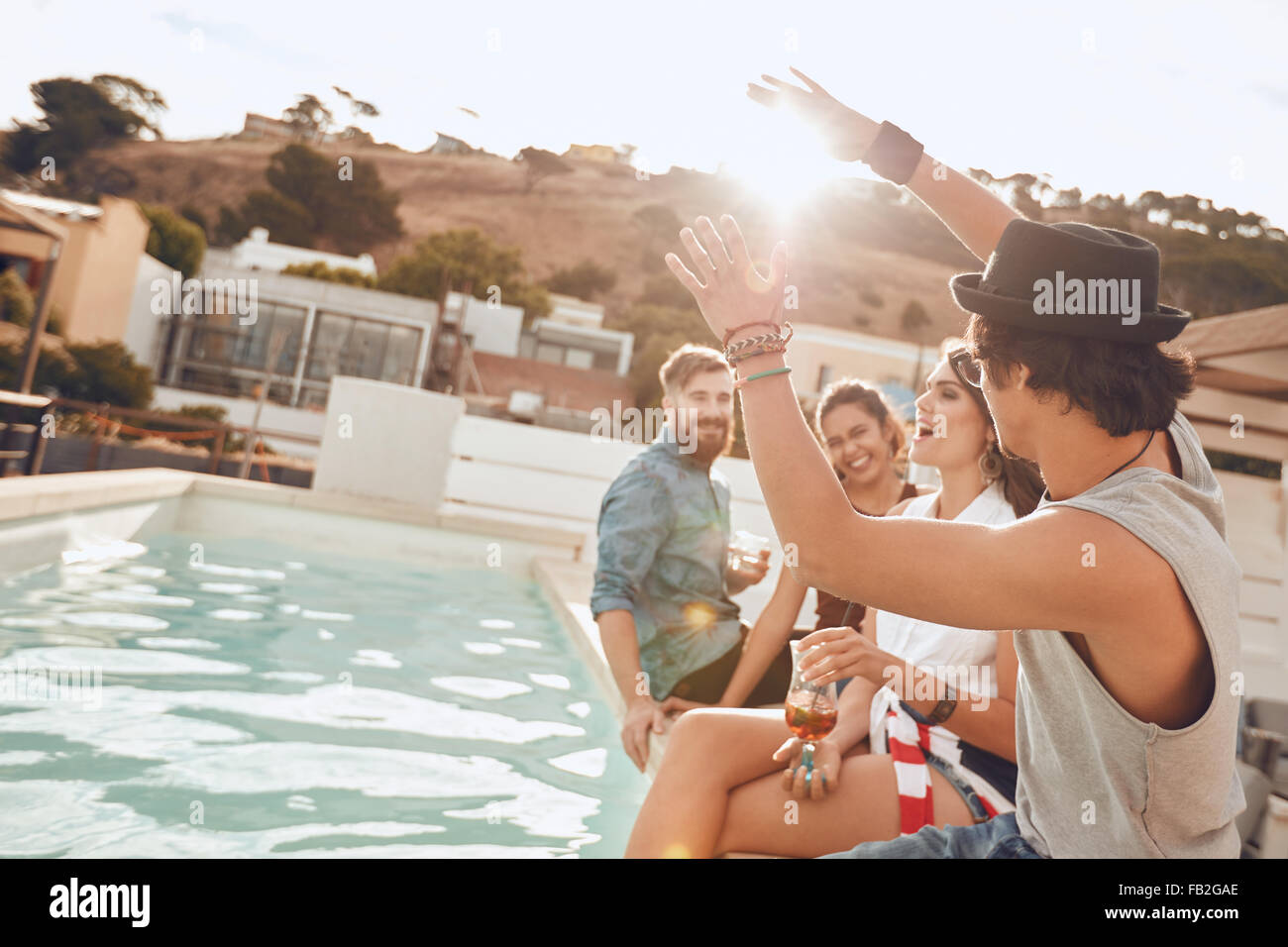 Young people sitting on the edge of the pool enjoying a party. Young woman singing during a the party. Multiracial - Stock Image