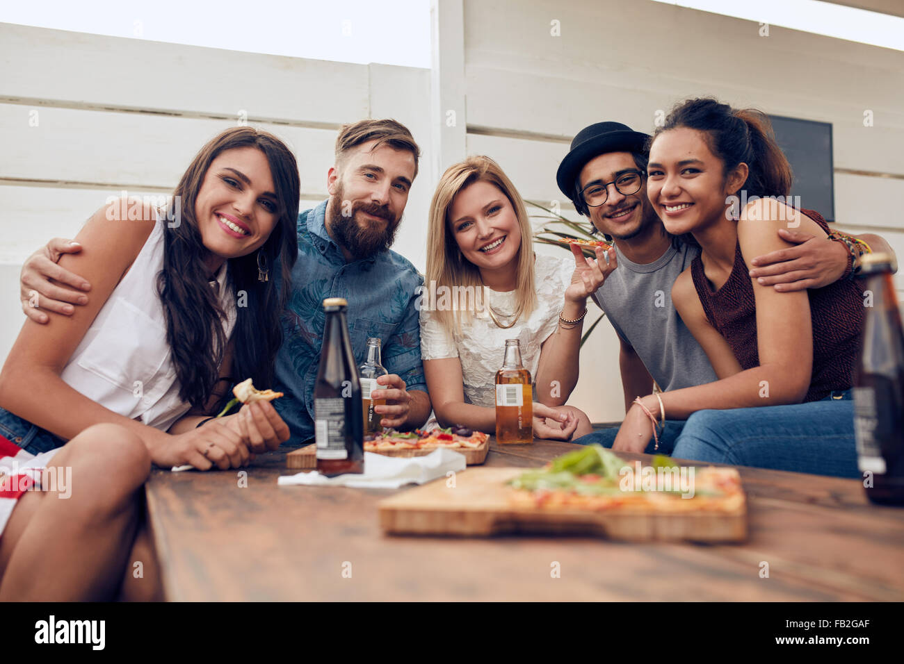 Group of friends gathered around the table at a roof party. Multiracial young people looking at camera and smiling. - Stock Image