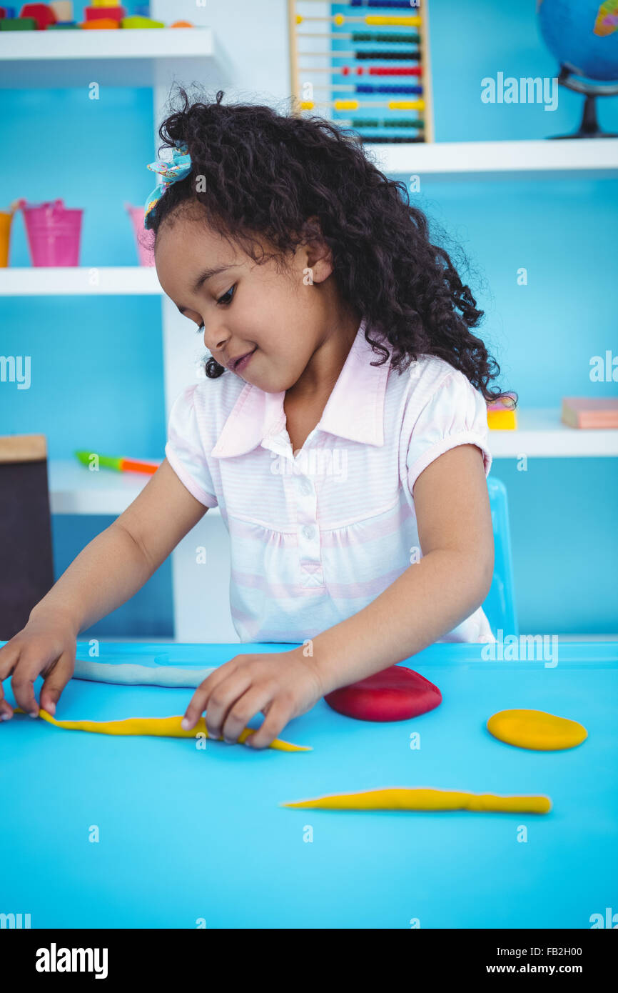 Cute girl playing with modeling clay - Stock Image