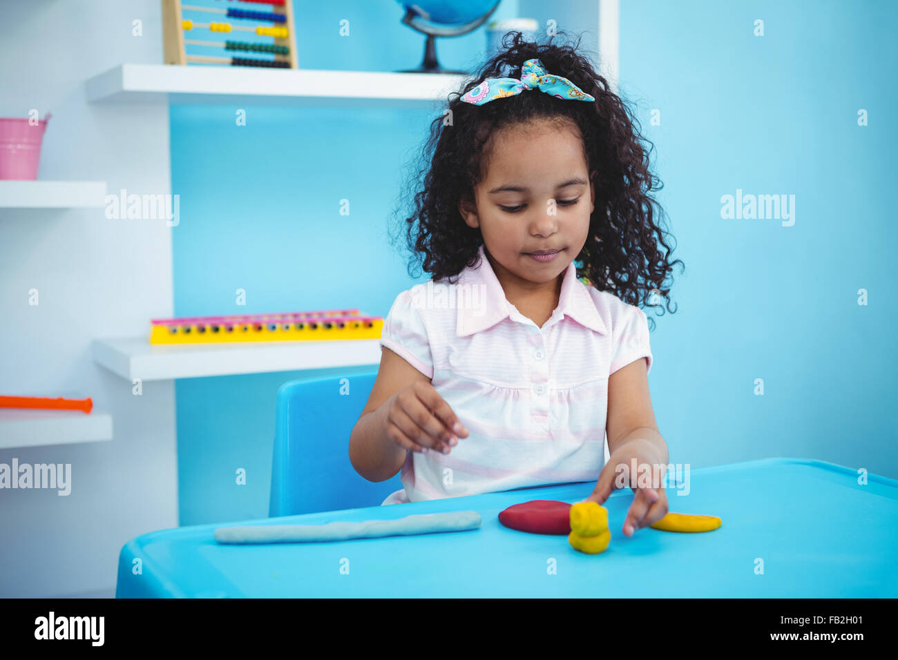 Cute girl using modeling clay - Stock Image