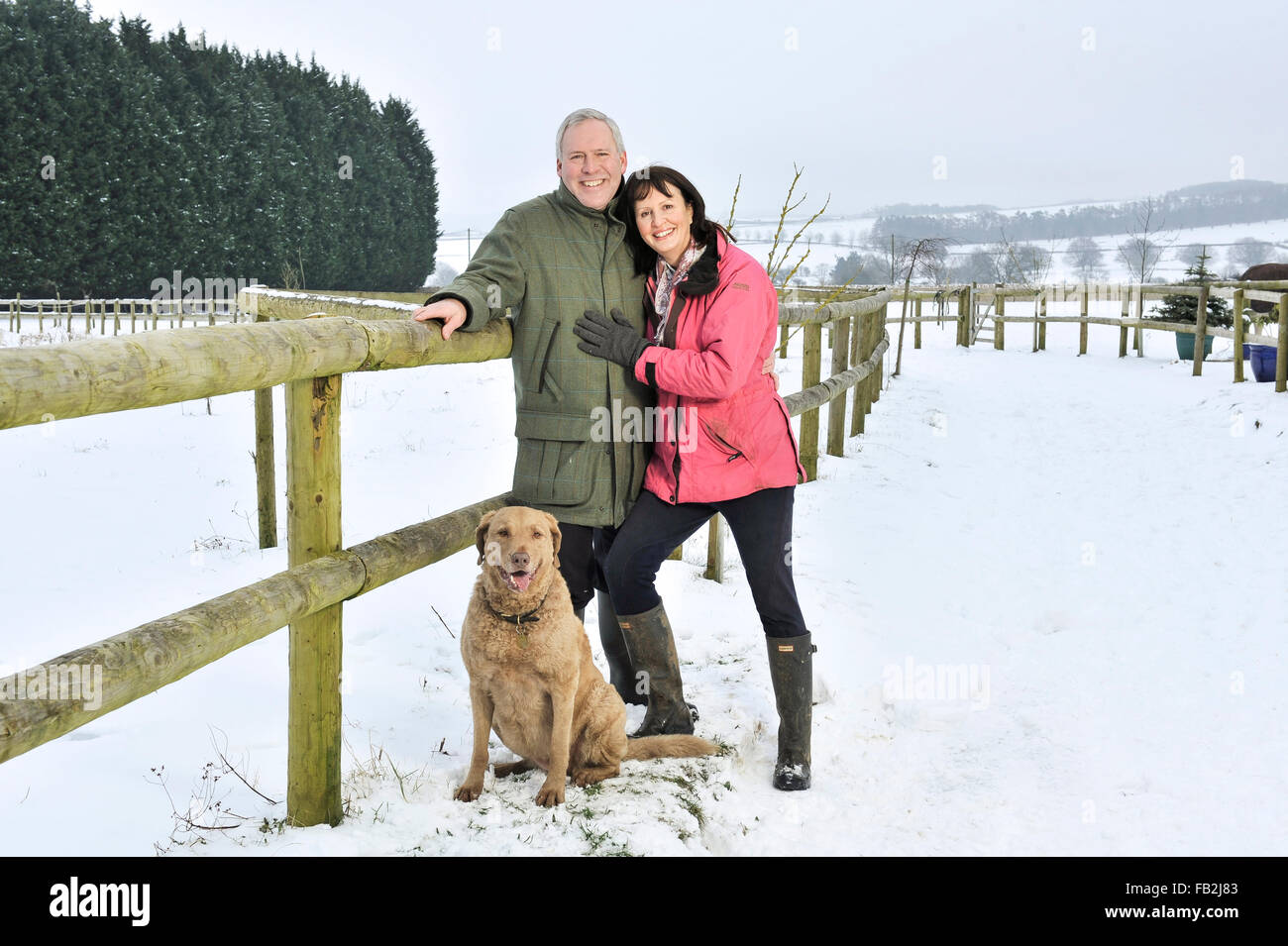 Middle aged couple walking their dog in a winter countryside - Stock Image